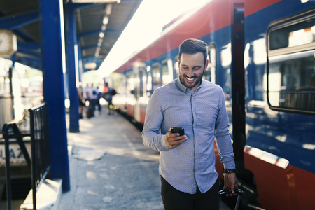Handsome man on train station with phone Stock fotó