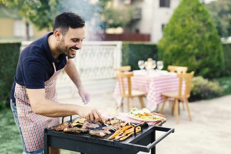 Handsome man preparing barbeque in the yard Stock fotó