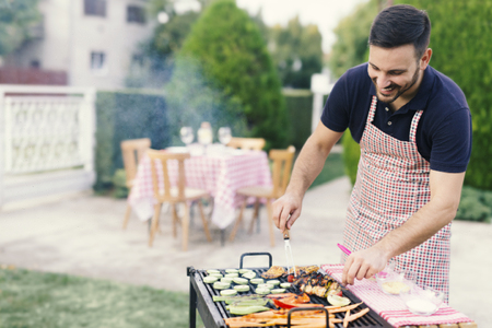 Young man preparing barbeque in the garden