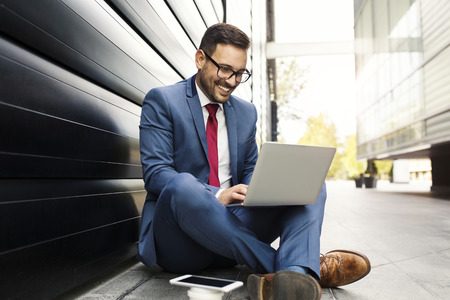 Businessman in suit sitting in front of the building and typing on laptop