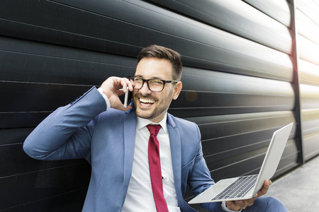 Businessman having phone call in front of the working space