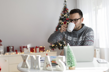 Freelancer working and drinking coffee during Christmas time