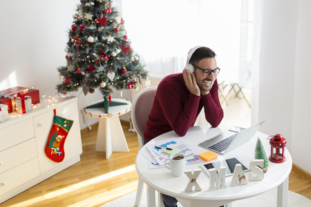 Freelancer working for Christmas and listening music Stock fotó