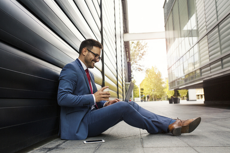 Happy smiling businessman sitting and relaxing in front of the office