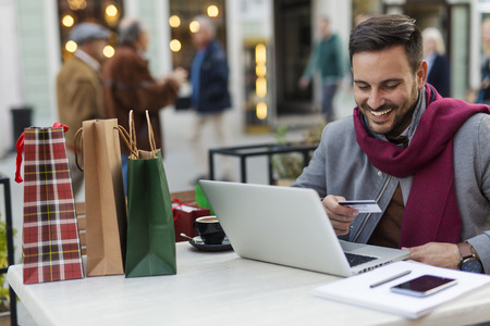 Man buying gifts online while he sitting in coffee shop