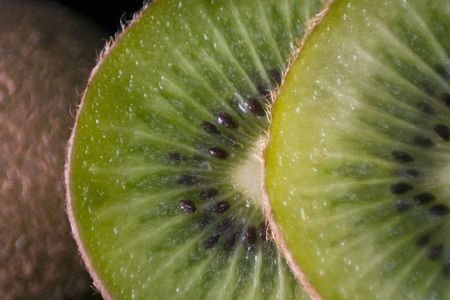 hairy pear: Slices of Kiwi (the fruit of Actinidia deliciosa) leaning against a whole fruit. Stock Photo