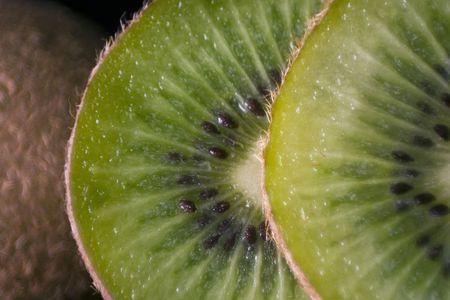 actinidia deliciosa: Slices of Kiwi (the fruit of Actinidia deliciosa) leaning against a whole fruit. Stock Photo