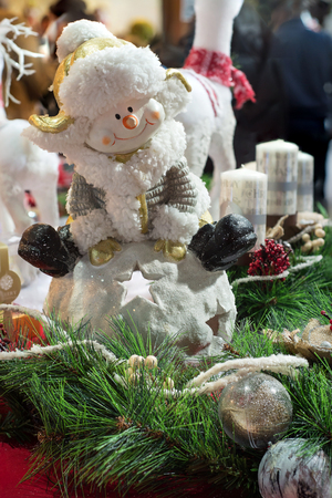 Snowman ceramic figure, christmas decoration with pine branch and christmas balls in foreground