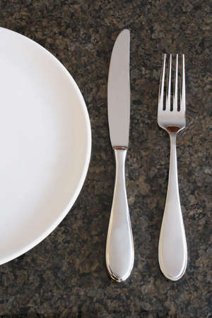 White Plate with Knife and Fork on Granite Surface