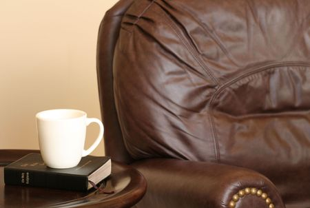 designer chair: Brown Leather Chair, Bible and Coffee Mug