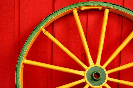 old wood farm wagon: Colored wagon wheel Stock Photo