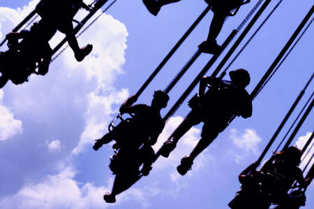 Silhouette of people on carnival swing photo