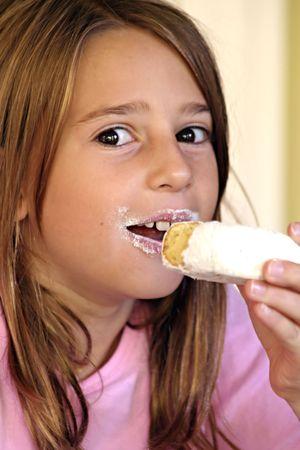 かわいい女の子を食べる粉末ドーナツ