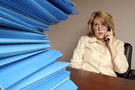 Woman Looking at File Folders while on the Phone