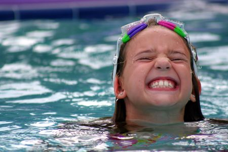 Cute girl making funny face in swimming pool