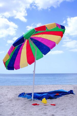 Colorful Beach Umbrella with Towel and Toys Stock Photo