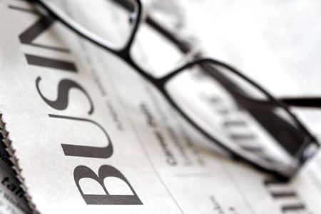 Business Section of a Newspaper with Reading Glasses photo