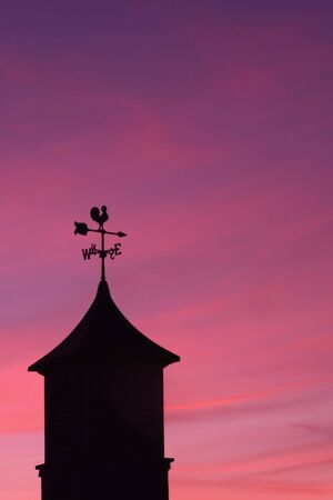 Weather Vane against Sunset Sky photo