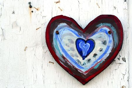 Colorfully painted heart on peeling white wooden wall Stock fotó
