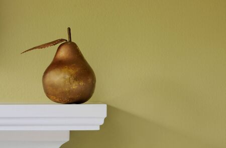 Fake gold colored pear on white mantle Banco de Imagens - 3818758