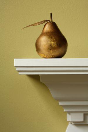 Fake gold pear on white mantle Banco de Imagens - 3830672
