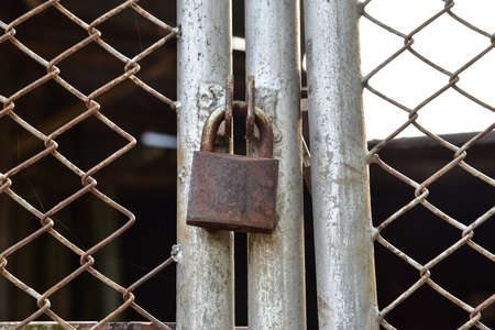 keep gate closed: rusty old lock. lock the fence