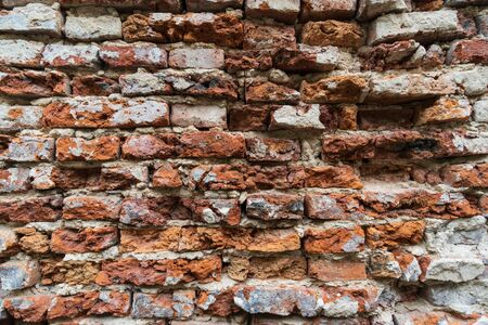 The old wall made of bricks and mortar are damaged, cracked concrete vintage wall background.