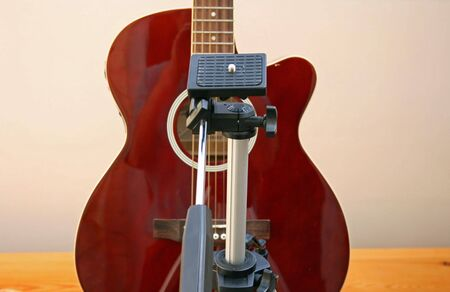 obscuring: a tripod obscuring the view of a guitar.