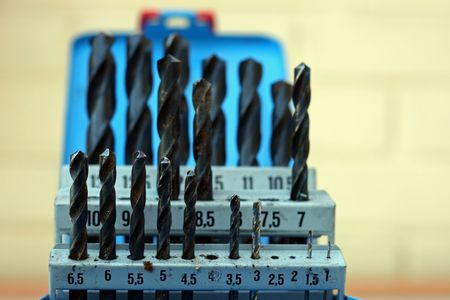 millimetres: set of large and small drill bits in a box.