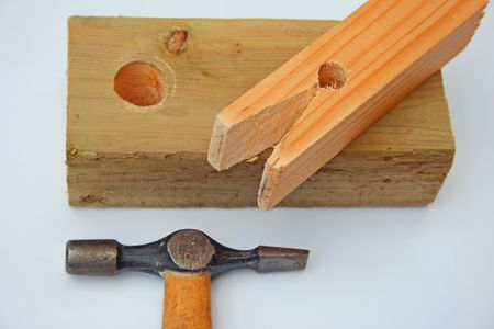 square peg,hammer and hole in a piece of timber. photo