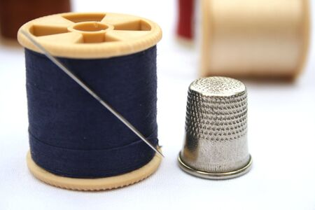 Reel of cotton with a needle and thimble.