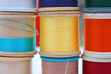 Stack of different coloured cottons on reels Imagens