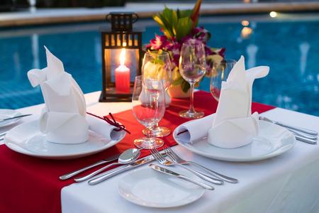 Mesa de cena romántica a la luz de las velas; Junto a la piscina con juego de mesa.
