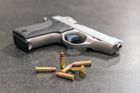 Handgun and Ammunition on Black Table