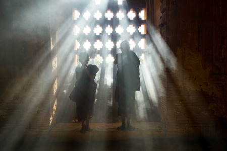 Silhouette of Two Young Monks Praying Inside Bhuddist Pagoda Temple in Bagan, Myanmar Stock Photo