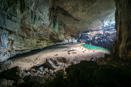 Hang En Cave - Tourists Camping Inside Large Cave in Vietnam. Cave with a beach, water lagoon and tents inside.