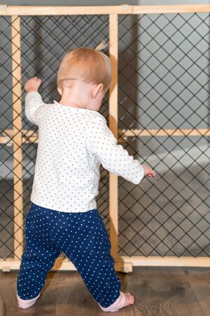 Cute Baby Standing Next to Safety Gate at Home Stock fotó