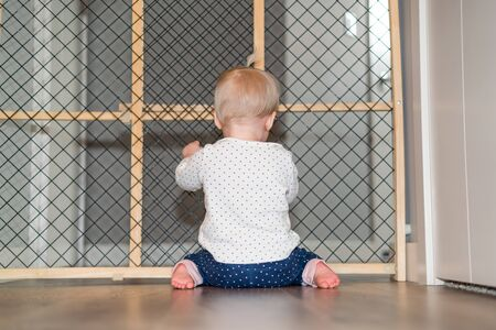 Cute Baby Playing Behind Safety Gate Stock fotó