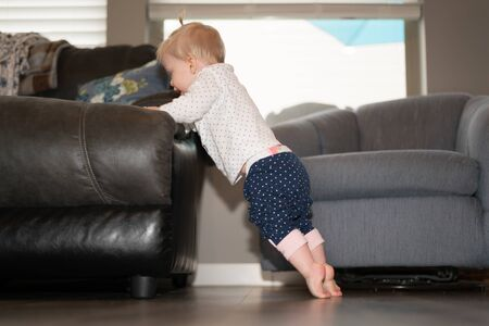 Cute Baby Girl Learning to Stand on Feet Stock fotó