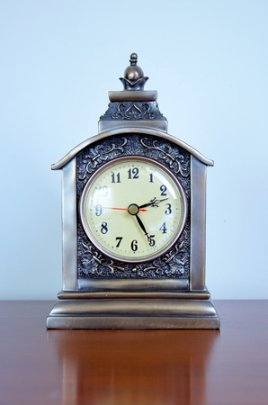 Beautiful, brown clock made of bronze staying on a wooden furniture