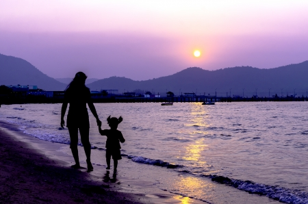 Silhouette of mother and baby walking on sunset photo