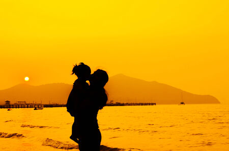 silhouettes of mother and baby kissing on sunset photo