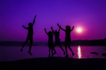 silhouette family jumping, sunset holiday photo