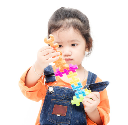Isolated asian kid girl playing with toys , white background Stock Photo