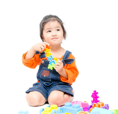 Isolated asian kid girl playing with toys , white background Foto de archivo