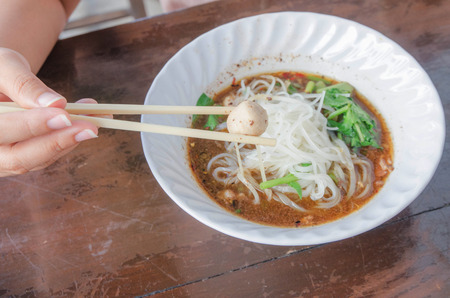 Hand holding chopstick take meatball, hot and spicy noodle photo