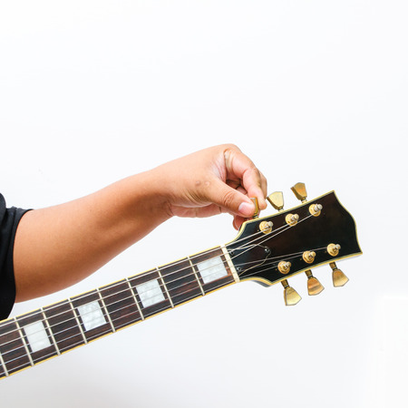 guitar tuner: Hand tuning the electric guitar on the white background