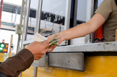 paying: Man paying money at toll booth in thailand Stock Photo