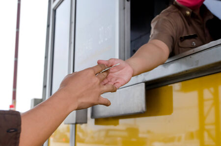 tollway: Man paying money at toll booth in thailand Stock Photo