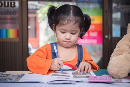 Ragazza asiatica scrivendo sul libro Archivio Fotografico - 28381797